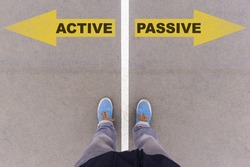 Active vs Passive text on yellow arrows on asphalt ground, feet and shoes on floor, personal perspective footsie concept