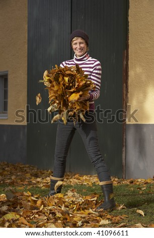 active woman collecting autumn leaves in the garden