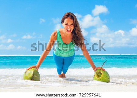 Active woman doing fitness exercise plank on coconut to keep fit and health. Beach surf background. Healthy lifestyle, morning workout, sport activity on summer family vacation in tropical island. #725957641