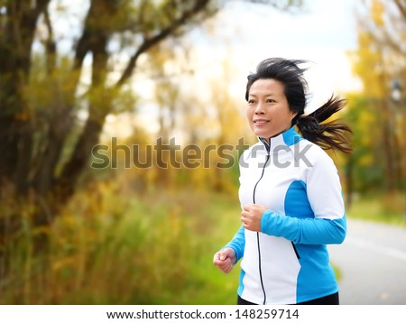 Active woman in her 50s running and jogging. Middle aged Asian mature female jogger outdoor living healthy lifestyle in beautiful autumn city park in colorful fall foliage. Asian Chinese adult fifties