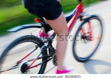 Active woman on a bike trip during summer. Lens blur