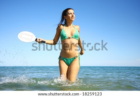 Active woman playing ball in the ocean