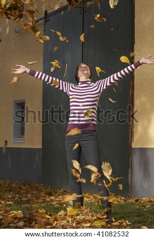 active  woman playing with autumn leaves in the garden