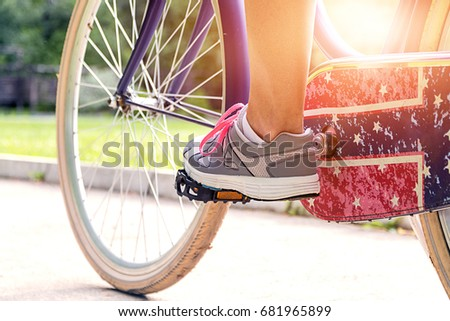 Active woman riding bicycle. Healthy lifestyle and recreation leisure activity. Cropped image of young riding bicycle in the nature. Low section shot of female athlete with her bike on country road.