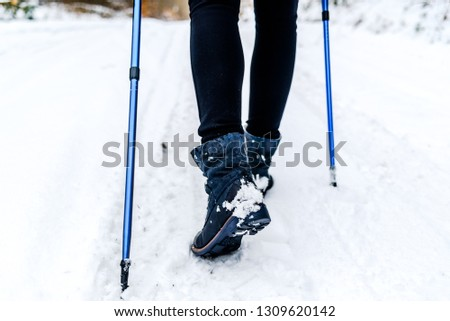 Active woman walking in snow. Shoes and legs detail. Outdoor activity, winter sport on snow with trekking sticks. #1309620142