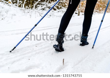 Active woman walking in snow. Shoes and legs detail. Outdoor activity, winter sport on snow with trekking sticks. #1315743755