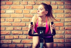 Active woman wearing sport bra working out,  using exercise bike at the gym. Sporty girl training in fitness center. Slim body weight loss concept.