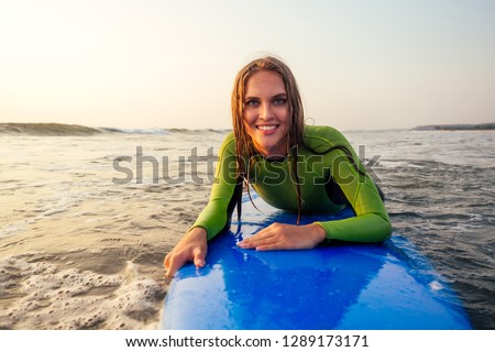 active women with surf board enjoy watersport at vacation holidays.sport girl in surfing school instructor of windsurf. tourist female model in a diving suit wetsuit on the beach in the Indian Ocean #1289173171