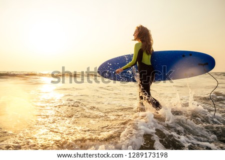 active women with surf board enjoy watersport at vacation holidays.sport girl in surfing school instructor of windsurf. tourist female model in a diving suit wetsuit on the beach in the Indian Ocean #1289173198
