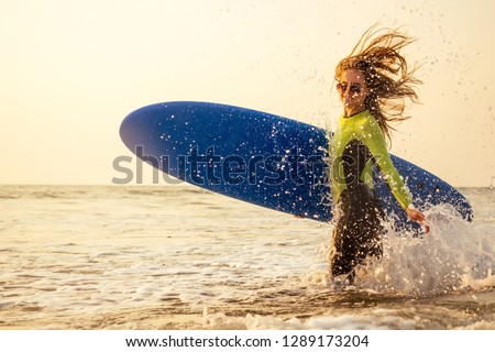 active women with surf board enjoy watersport at vacation holidays.sport girl in surfing school instructor of windsurf. tourist female model in a diving suit wetsuit on the beach in the Indian Ocean #1289173204