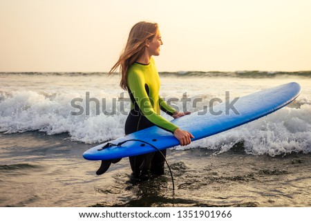 active women with surf board enjoy watersport at vacation holidays.sport girl in surfing school instructor of windsurf. tourist female model in a diving suit wetsuit on the beach in the Indian Ocean #1351901966