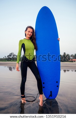 active women with surf board enjoy watersport at vacation holidays.sport girl in surfing school instructor of windsurf. tourist female model in a diving suit wetsuit on the beach in the Indian Ocean #1351910216