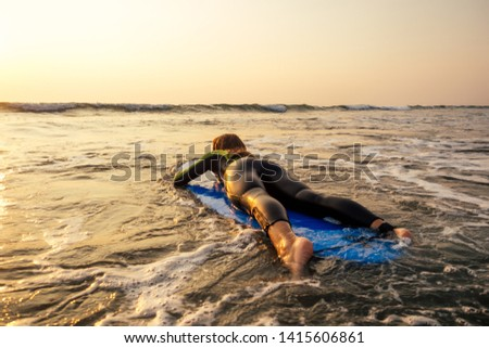 active women with surf board enjoy watersport at vacation holidays.sport girl in surfing school instructor of windsurf. tourist female model in a diving suit wetsuit on the beach in the Indian Ocean #1415606861