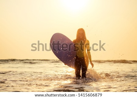 active women with surf board enjoy watersport at vacation holidays.sport girl in surfing school instructor of windsurf. tourist female model in a diving suit wetsuit on the beach in the Indian Ocean #1415606879
