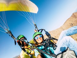 Active young adult people woman enjoy paraglide activity fliying in the sky with professional pilote in the back - cheerful happy female people fly and have fun with paragliding