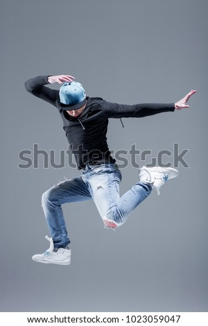 Active young beautiful hip-hop dancer man jump in fly at studio, copy space, motion shot. Grey background #1023059047