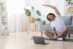 Active young cheerful man doing morning gymnastic at home, sitting on yoga mat and stretching, copy space