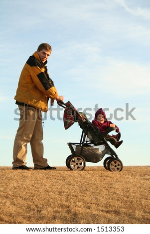active young dad with his child in a stroller happy to take a walk in the park on a sunny day, against blue sky