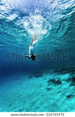 Active young female dancing underwater, enjoying summer vacation in blue transparent water, dive to the bottom of sea, enjoyment and freedom concept #226761970