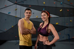 Active young man and woman in sportswear looking at camera, standing against climbing wall. Concept of sport life and rock climbing. Horizontal shot. Selective focus