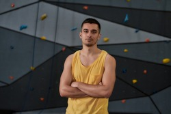 Active young man in sportswear looking at camera, standing against climbing wall. Concept of sport life and rock climbing. Horizontal shot. Focus on man