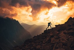 Active young man run on the top of the hill. Sunset mountains in background. Slovakia, High Tatras