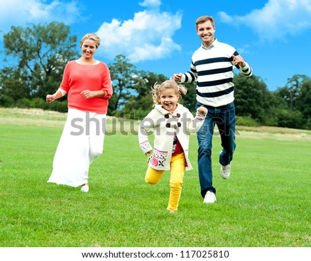 Active young parents running to catch their daughter. Fun loving family