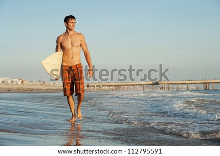 active young surfer holding a surfboard at the beach