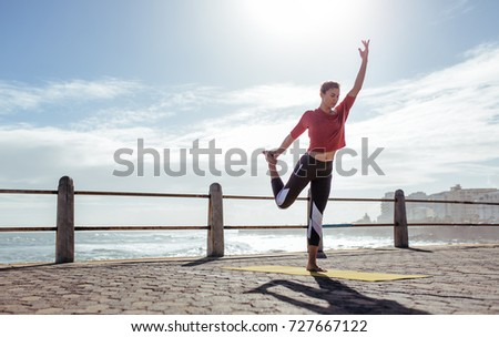 Active young woman doing stretching exercises outdoors. Fitness woman exercising in yoga pose on the road by the sea. #727667122