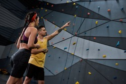 Active young woman in sportswear going to climb, male instructor helping her, standing against artificial training climbing wall. Concept of sport life and rock climbing. Selective focus