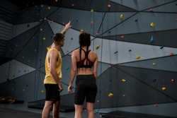 Active young woman in sportswear going to climb, male instructor helping her, standing against artificial training climbing wall. Concept of sport life and rock climbing. Rear view. Selective focus