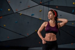 Active young woman in sportswear looking aside, standing against artificial training climbing wall. Concept of sport life and rock climbing. Horizontal shot. Focus on woman