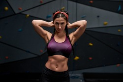 Active young woman in sportswear looking at camera, showing her sportive body, abs, standing against artificial training climbing wall. Concept of sport life and rock climbing. Focus on person