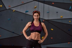Active young woman in sportswear looking at camera, standing against artificial training climbing wall. Concept of sport life and rock climbing. Horizontal shot. Focus on woman