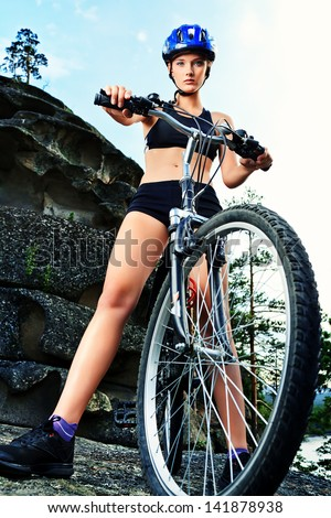 Active young woman rides a bike in the mountains.