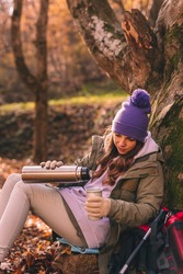 Active young woman sitting in the forest, leaning on the tree, taking a hiking break, relaxing outdoors on a sunny autumn day and pouring a cup of hot tea from a vacuum flask