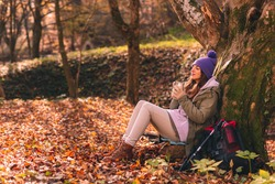 Active young woman sitting in the forest, leaning on the tree, taking a hiking break, relaxing outdoors on a sunny autumn day and drinking a cup of hot tea