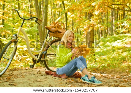 Active young women walks in autumn forest park and holds autumnal fall yellow leaves. Stylish blonde girl cycle at autumn sunny forest. Vintage bike with basket. Outdoor activity concept
