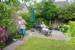 Actively retired Dutch seniors in a Typical display of gender roles where the Wife is gardening and the husband is relaxing and having a beer