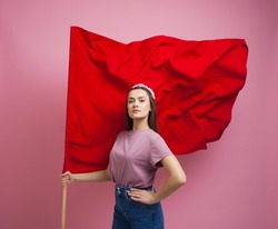 activist and revolutionary, young woman with a red flag on a pink background. Feminism and the struggle for rights, concept