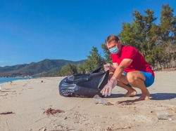 Activist volunteer Man in medical face mask pick up garbage that pollute beach sand near sea. Problem of spilled rubbish trash caused by man-made, planet pollution and environmental protection concept