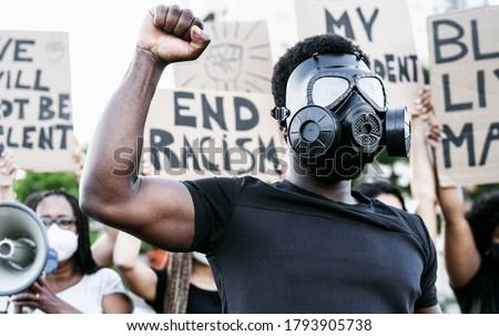 Activist wearing gas mask protesting against racism and fighting for equality - Black lives matter demonstration on street for justice and equal rights - Blm international movement concept