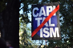 Activists holding capitalism sign on the poster at the protests.