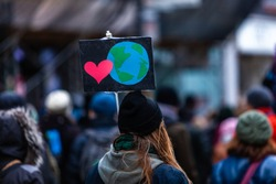Activists marching for the environment. French sign seen in an ecological protest with a planet earth and a heart. Shot from behind