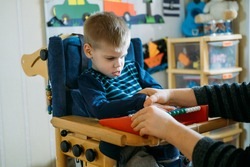 Activities for kids with disabilities. Preschool Activities for Children with Special Needs. Boy with with Cerebral Palsy in special chair play with mom at home.