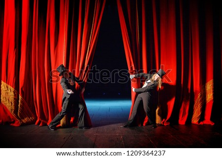 Actor and actress in tuxedos open theater curtain