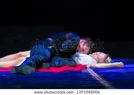 Photo of  Actor and actress in white costumes play a romantic image on the stage of the theater.