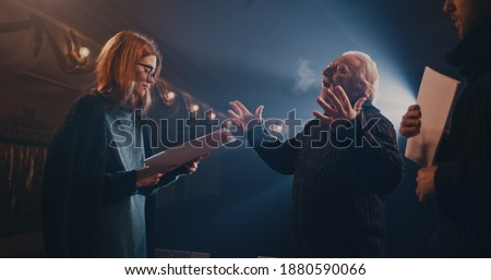 Actor and actress with scripts holding hands and speaking with each other while rehearsing romantic scene with director on stage in theater
