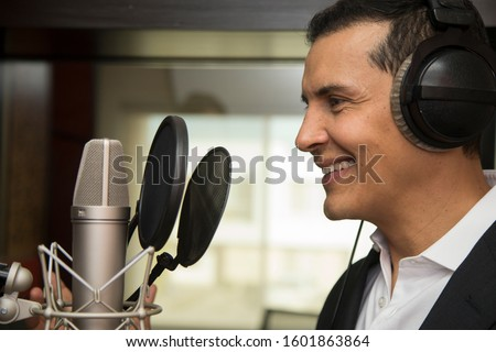 actor and radio announcer with headphones and microphone working film dubbing, performing radio spot and singing Stok fotoğraf ©