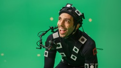Actor Wearing Motion Caption Suit and Head Rig acts as an Animal or a Monster for CGI Green Screen Scene. Big Budget Filmmaking On Film Studio Set Shooting Blockbuster Movie with Chroma Key.